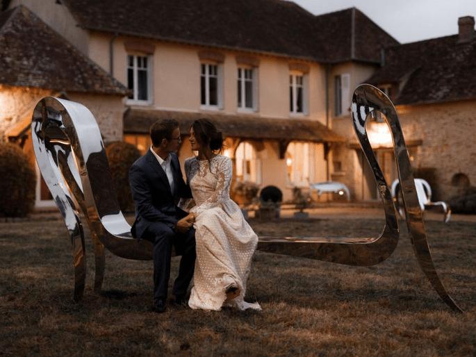 Un couple qui profite des espaces extérieurs du Domaine de la Thibaudière assis sur une vraie œuvre d'art