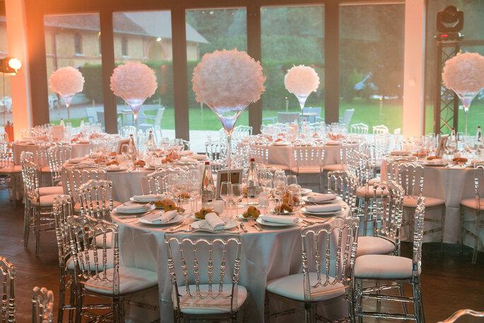Une salle décorée pour un mariage avec des vases remplis de fleurs blanche et des chaises transparentes avec vue sur le jardin