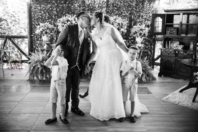 Casal se beijando e crianças tampando os olhos em cerimônia de casamento.