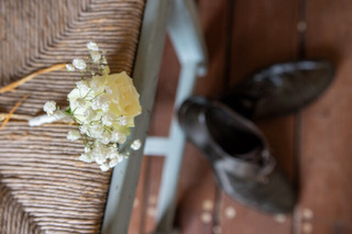 La boutonnière faite de fleurs fraiches et les chaussures du marié