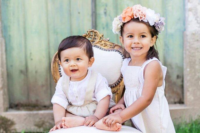 menino bebé e menina com coroa de flores vestidos de festa