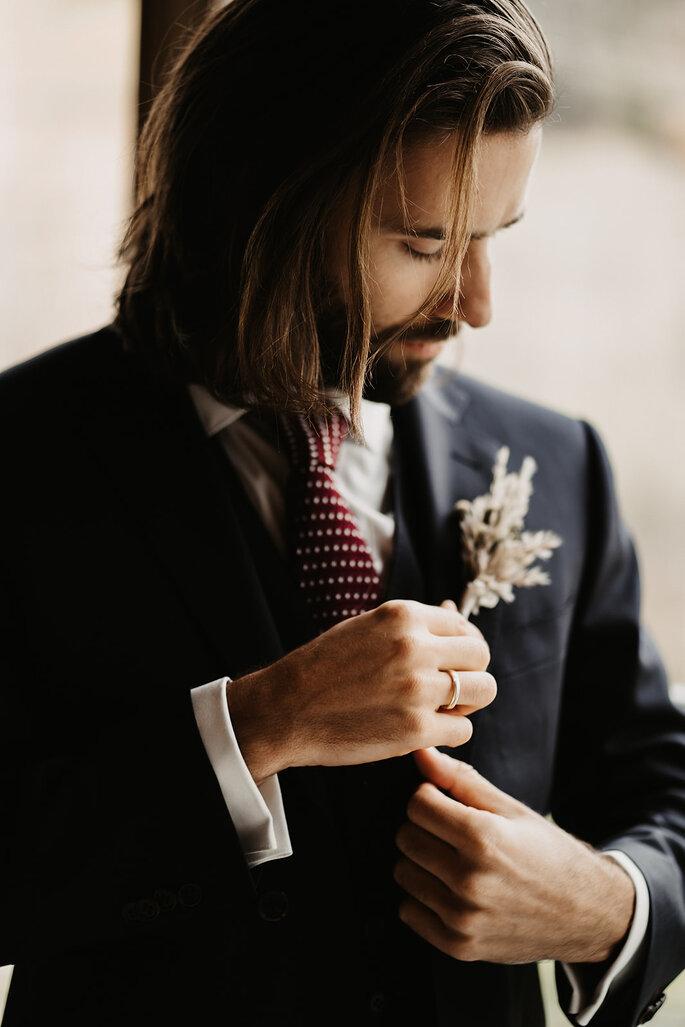 Der Bräutigam steckt sich die Boutonniere an.