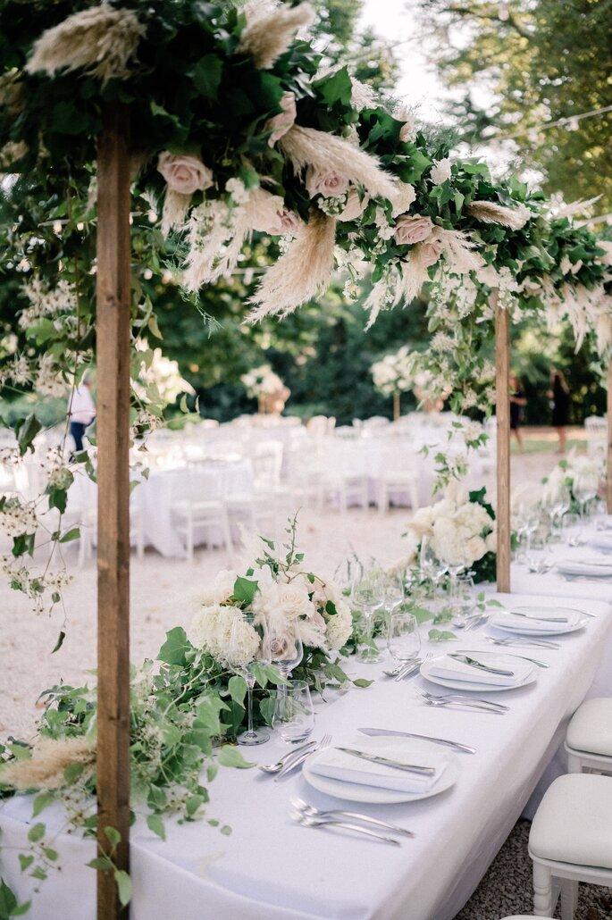 My Wedding in Provence, table dressée avec un énorme bouquet et des arches de fleurs