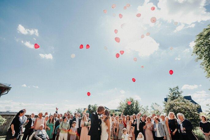 Die Hochzeitsgesellschaft lässt Luftballons mit Wünschen steigen.