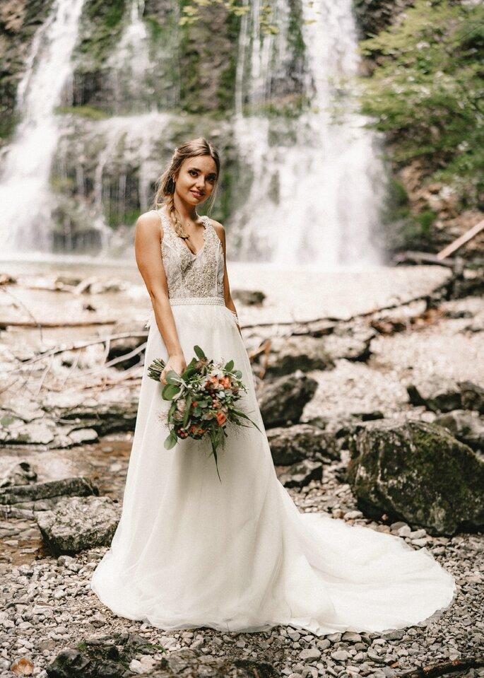 Braut steht vor Wasserfall und lächelt in die Kamera.
