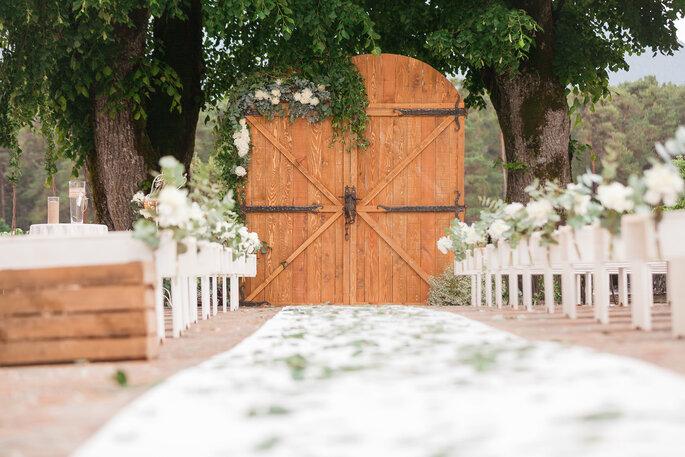 Une cérémonie laïque va avoir lieu dans un parc arboré, un tapis blanc est posé sur le sol et les bancs blanc sont décorés de fleurs blanches tandis que l'arche de cérémonie est en forme de portes