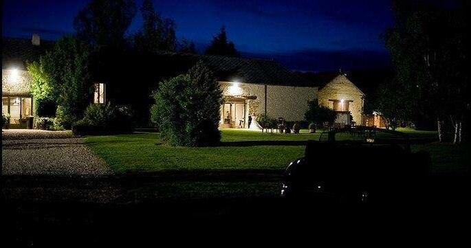 La Ferme du Grand Chemin éclairée dans la nuit, on distingue sa façade de pierre et ses jardins dans la pénombre