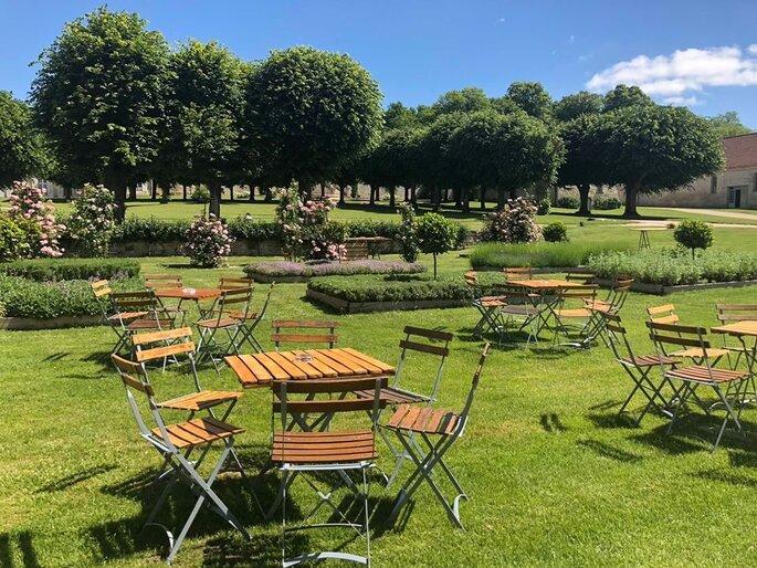 Table en bois et chaises disposées dans le parc du Château de Serans avec des arbres en arrière plan et des rosiers