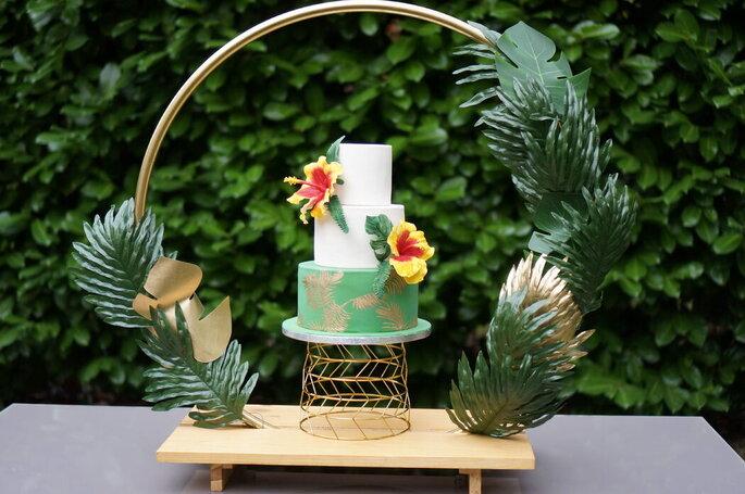 Gâteau de mariage décoré avec des fleurs jaunes, exposé sur le buffet de mariage.