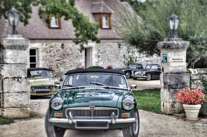 Des voitures de collection sortent de la cour d'une belle propriété