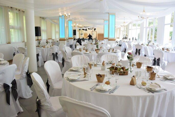 Une salle de réception de mariage prête à recevoir les invités, baignée de lumière naturelle
