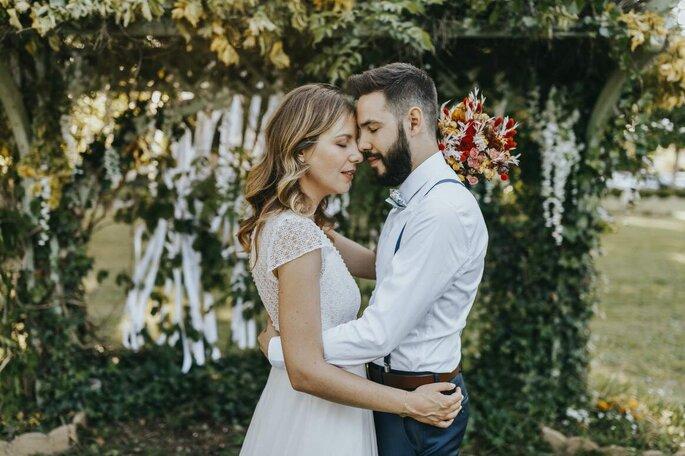 Un couple de mariés enlacés devant une arche de verdure et de rubans