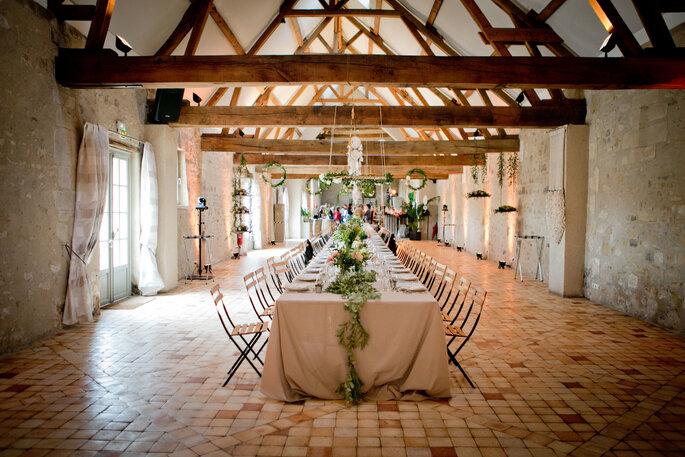 Une jolie table avec une nappe blanche et une décoration végétale dressée dans une salle de réception intérieure