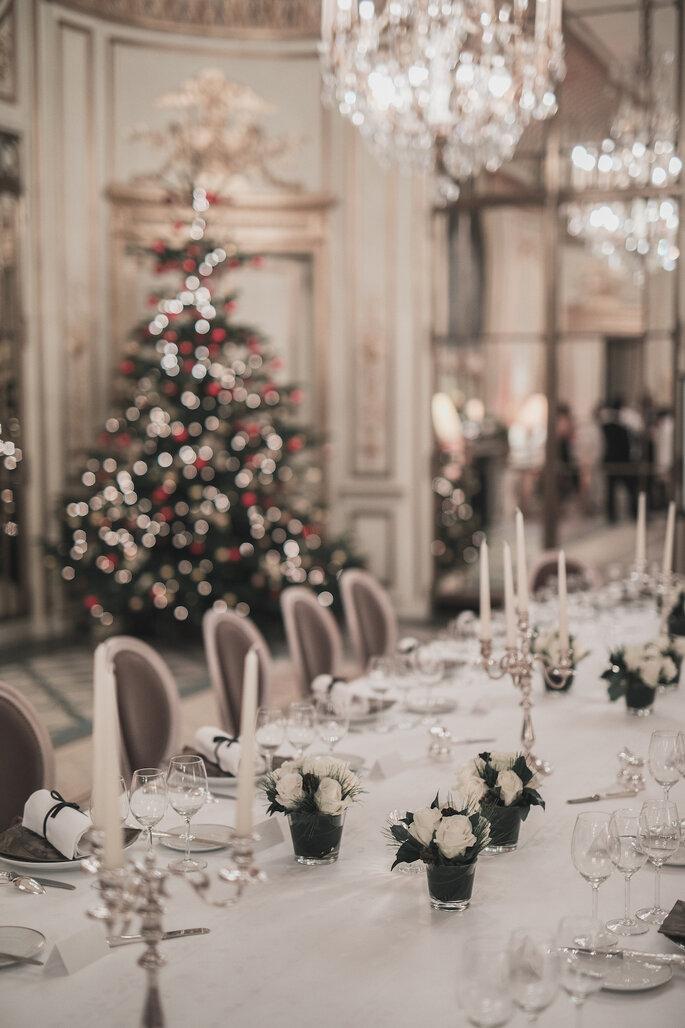 Une table de mariage dans un décor de Noël, avec un sapin en arrière-plan.