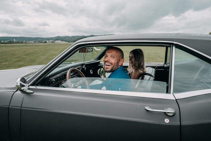Bräutigam aus Hochzeitsauto lächelnd