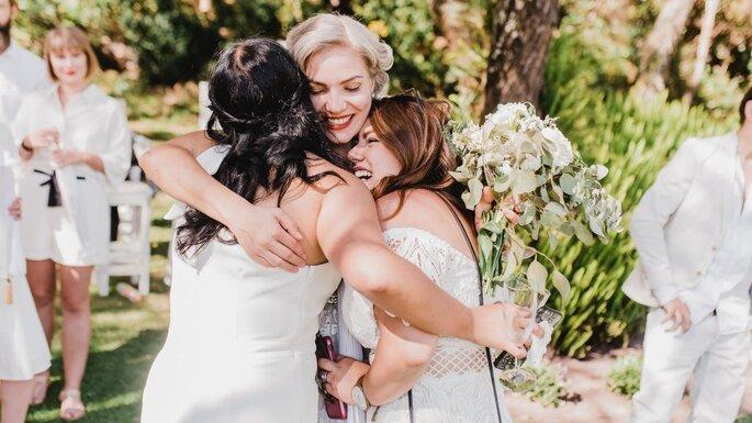 damas de honor abrazando a la novia el día de su boda felices