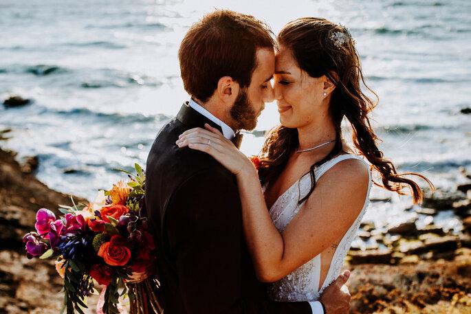 dois noivos agarrados com o mar como fundo