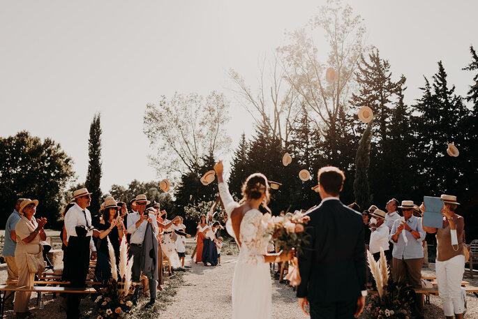 Les invités lancent leurs chapeaux de pailles dans les airs à la fin d'une cérémonie de mariage