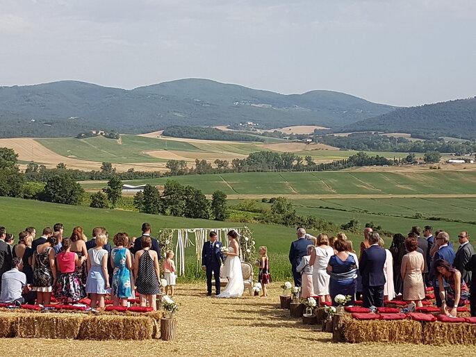 Un couple de mariée devant l'arche de cérémonie et avec derrière eux, leurs invités. Ils font tous face aux collines de la région pour leur cérémonie laïque.