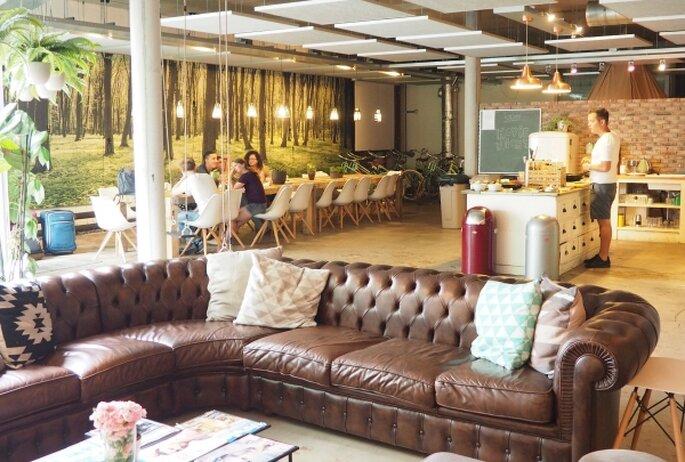 Hall do Hostel Ecomama em Amsterdamcom sofá em couro, mesa e cadeiras para café da manhã.
