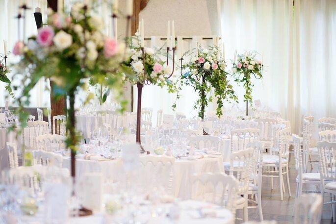 Tables blanches dressées pour un mariage avec des chandeliers de fleurs au lieu de réception la Ferme du Grand Chemin dans le Val d'Oise