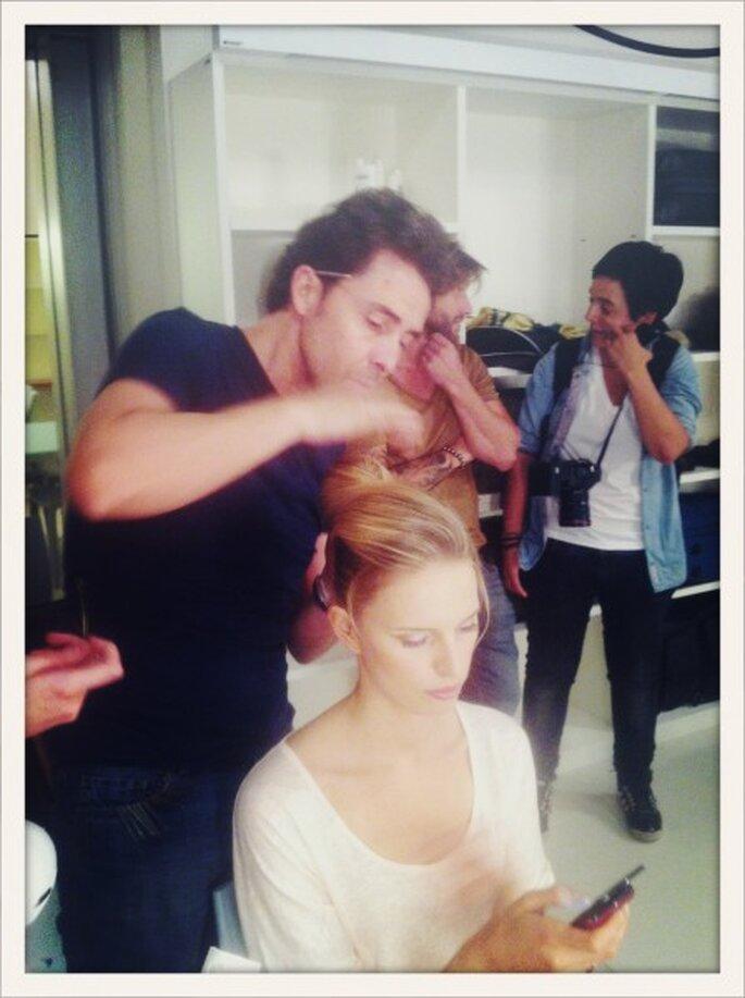 Moncho Moreno, director de estilismo de Pronovias, peina a Karolina Kurkova mientas la modelo utiliza su móvil.