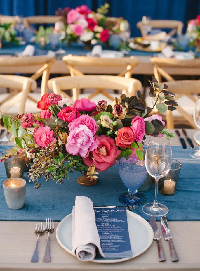 Centros de mesa llenos de colores llamativos en tonos rojos y rosas, flores naturales