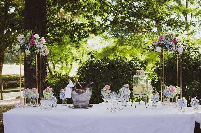 Une table est dressée dehors dans le parc avec de multiples bouquets de fleurs colorées pour un banquet