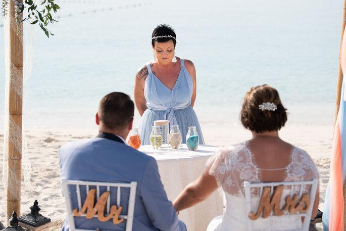 Une officiante de cérémonie d'engagement exécute un rituel devant des mariés sur une plage