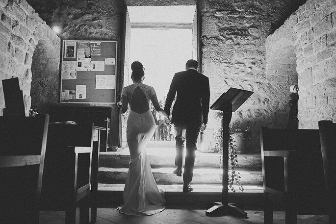 Les mariés se dirigent vers la sortie de l'église, main dans la main