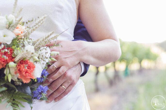 Détail d'un couple de mariés enlacé, zoom sur leurs alliances et le bouquet