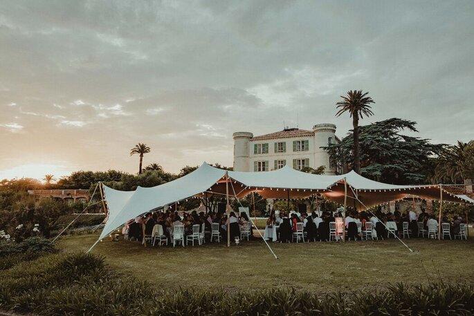 Une réception de mariage sous une tente nomade ornée de lampions, avec un château en toile de fond