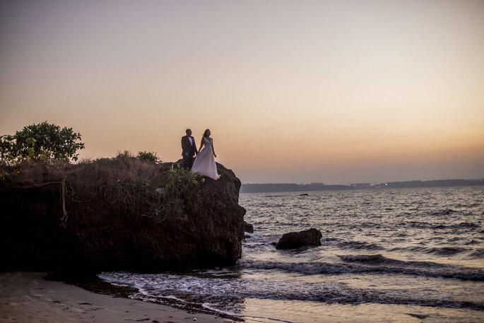 Deux mariés au bord d'une falaise surplombant l'océan devant un coucher de soleil