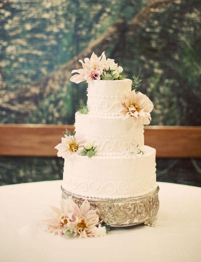 Pastel de boda blanco y sofisticado, decorado con flores en tonos marfil y rosa quemado