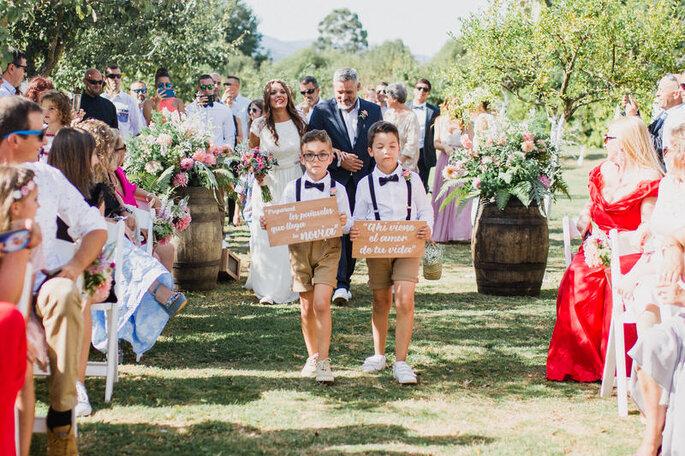 entrada da noiva pajens com placas com bermudas e laço