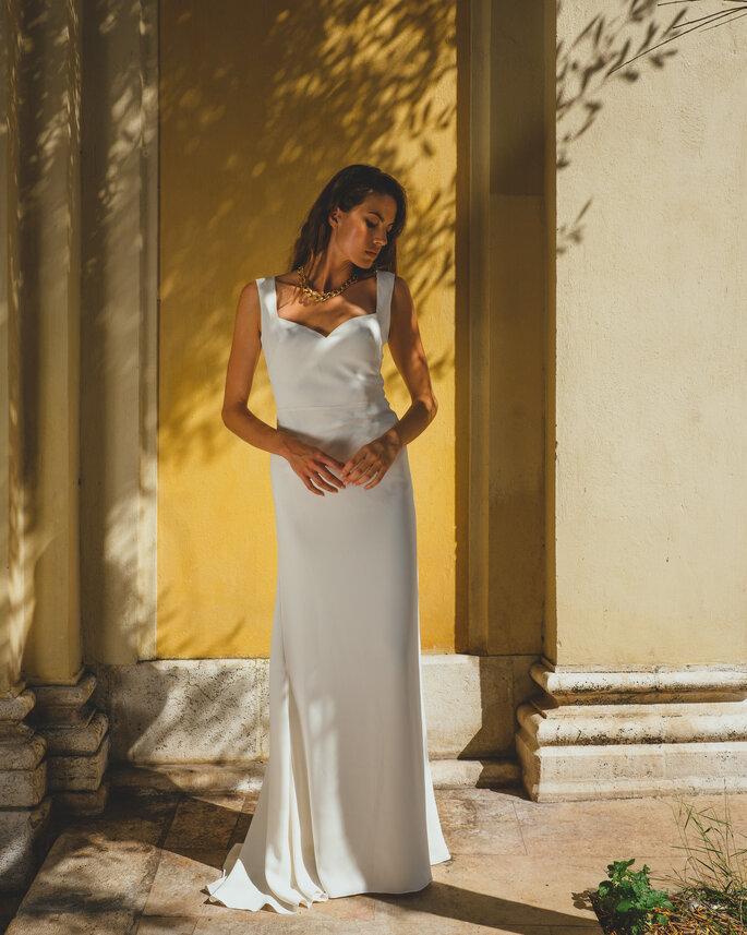 Une mariée porte une robe longue simple et minimaliste, avec une belle coupe et adaptée à sa morphologie