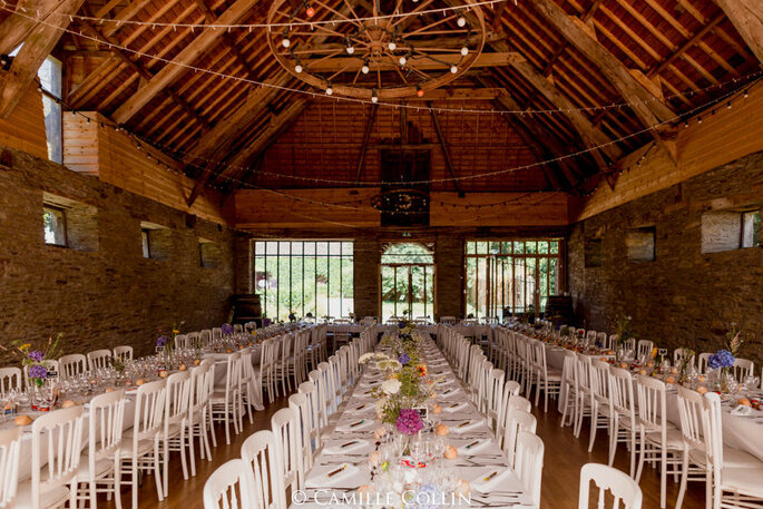 Salle aménagée dans le Manoir de la Fresnaye avec des tables et chaises blanches, des murs de pierres apparentes et des poutres en bois