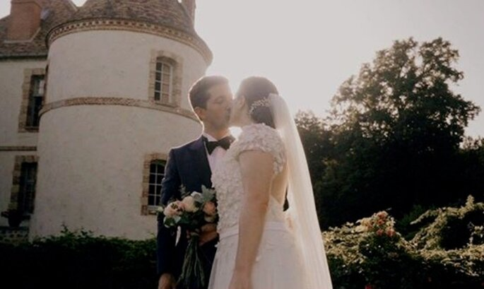 Un couple de mariés s'embrasse devant un château ancien.