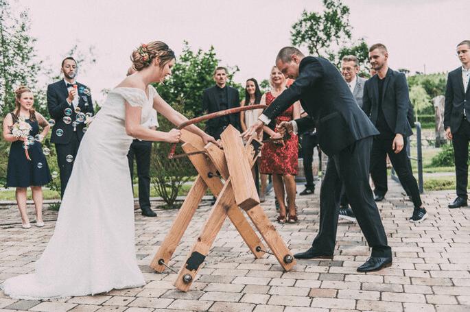 Brautpaar zersägt einen Baumstamm