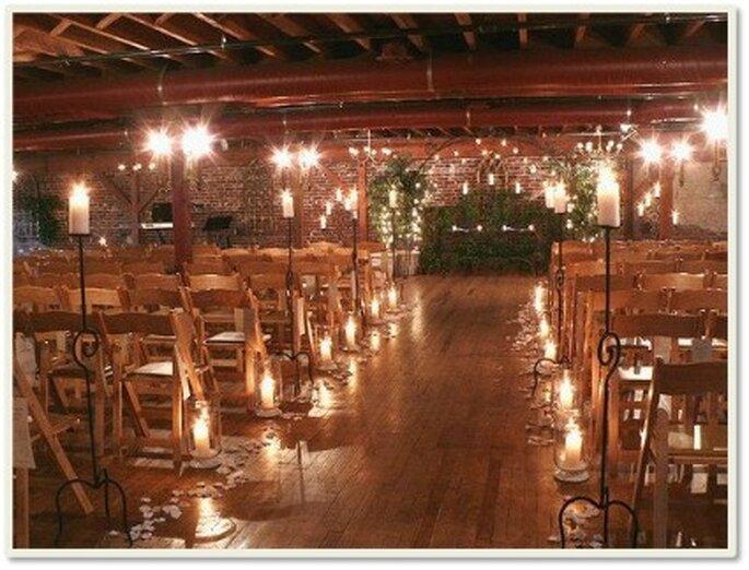 Candeleros de cristal con velas sobre el piso para iluminar el camimo de los novios
