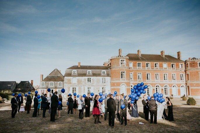 Des invités attendent avec un ballon bleu à la main à l'extérieur du Château de Denonville les futurs mariés