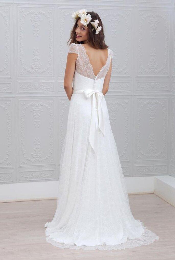 Une mariée portant une robe en dentelle avec un noeud ainsi qu'une couronne de fleurs
