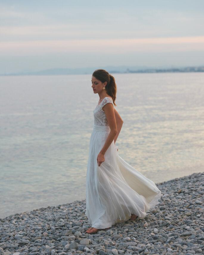 Une mariée près de la mer tenant sa robe fluide et longue à deux mains