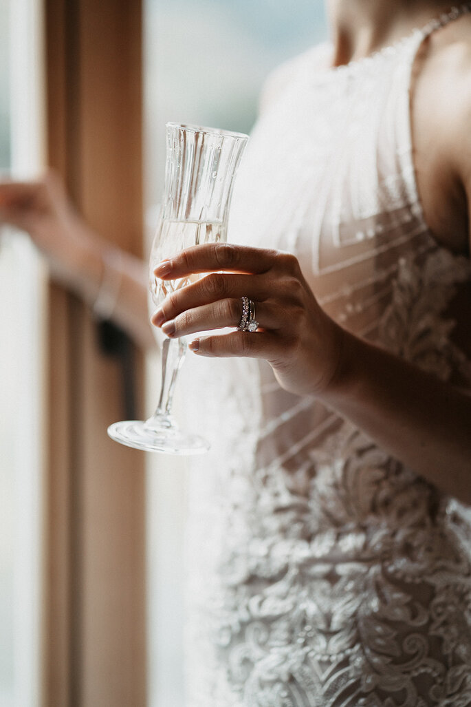 Die Braut feiert mit einem Glas.