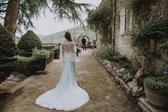 Une mariée porte une robe longue en dentelle avec un dos nu pour un mariage champêtre