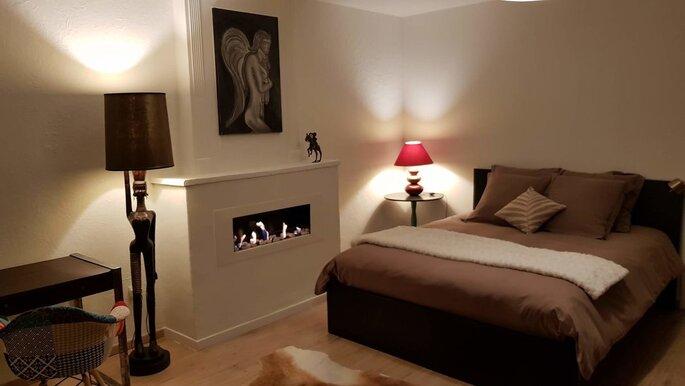Chambre dans les tons marron, beige et taupe, avec un lit, une fausse cheminée, un tableau d'ange et des lampes