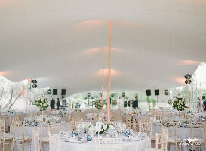 Un banquet de mariage dressé sous une tente luxueuse, les tables sont fleuries et décorées