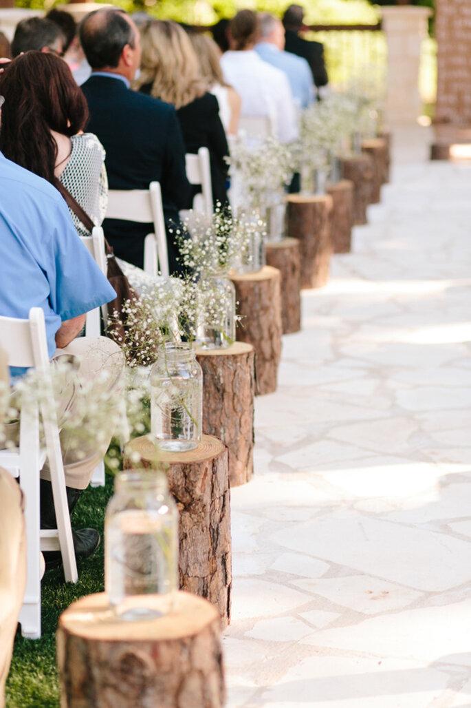 Decoración de las sillas con flores y troncos de madera.