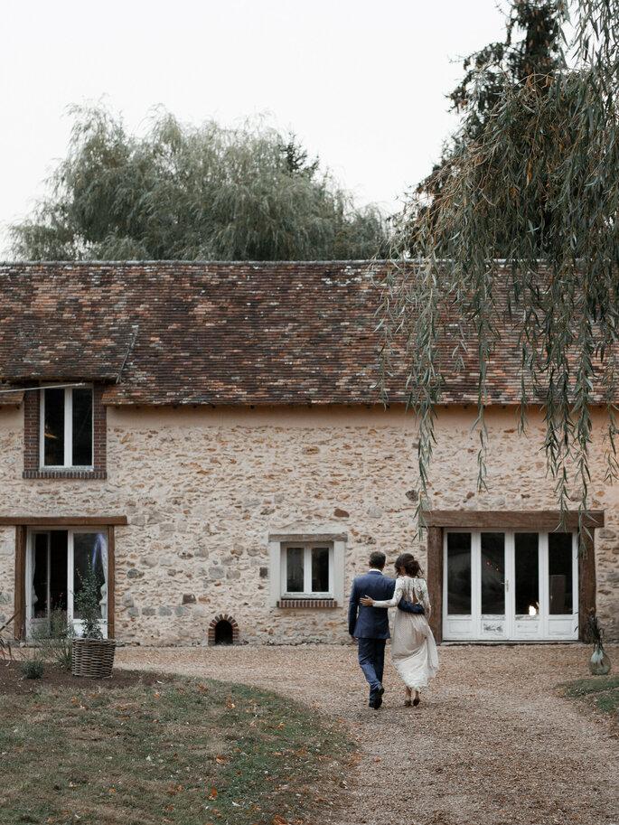 Un couple bras dessus bras dessous qui s'avance vers la demeure du Domaine de la Thibaudière
