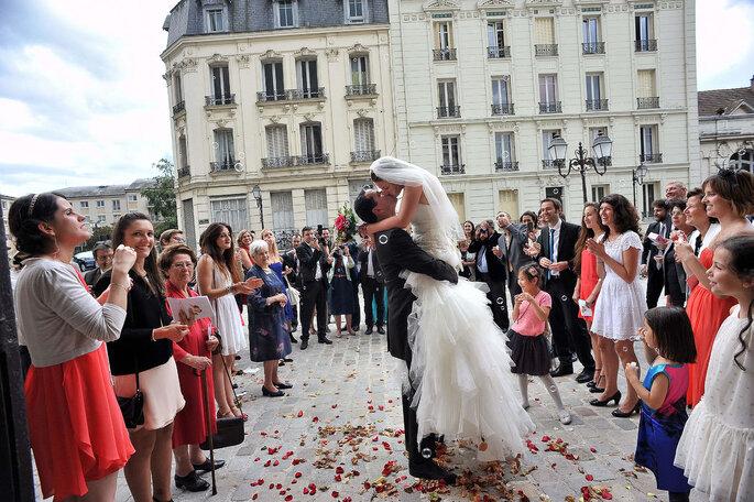 Baiser d'un couple de mariés devant leurs invités